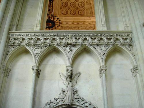 Un des trnçons du déambulatoire, avec 4 arcs brisés au-dessus d'un ange en pleurs