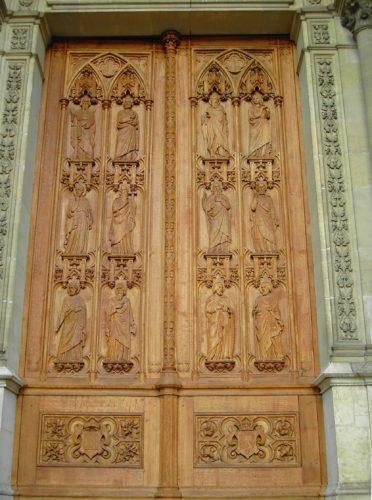 Porte en chêne, avec une lancette sur chaque vantail, chacune étant divisée en six niches avec une figure d'apôtre dans un décor gothique